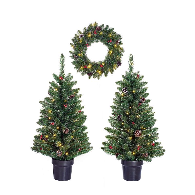 Kerstdecoratie verlichte en versierde krans en boompjes voor de voordeur