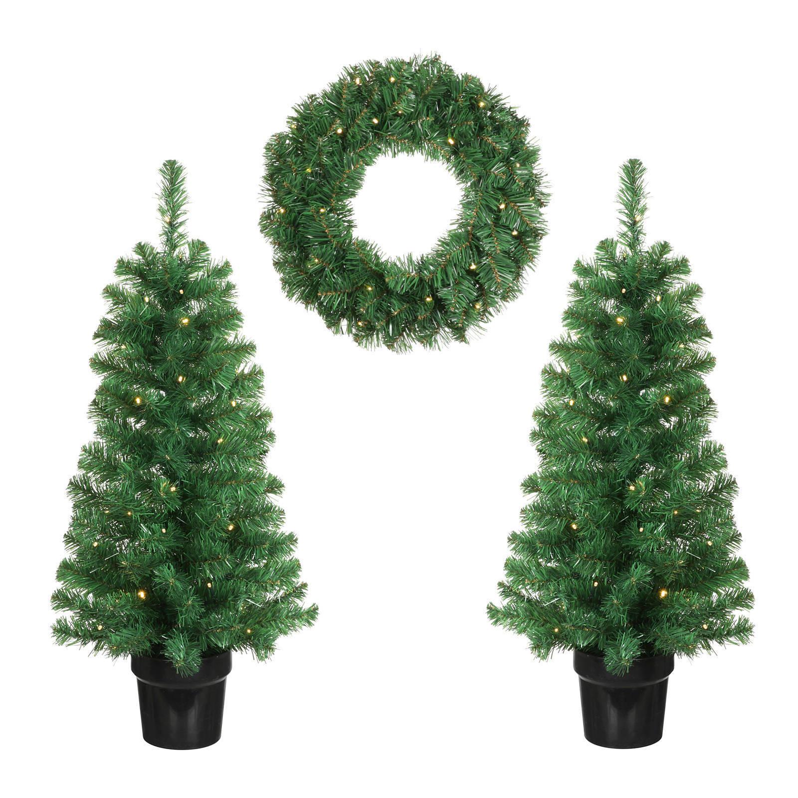 Kerstdecoratie verlichte krans en boompjes voor de voordeur